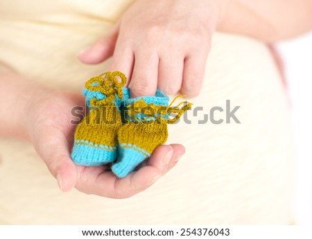 Pregnant woman holding knitted baby socks in room closeup