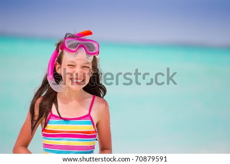 Pretty, smiling girl with swimwear and snorkel at a tropical beach.