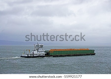 pusher tug full of wood chips sailing up the Columbia river in Astoria Oregon