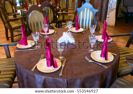Round table laid out with a brown cloth. On the table for four devices: plates, napkins, cups, knives and forks.