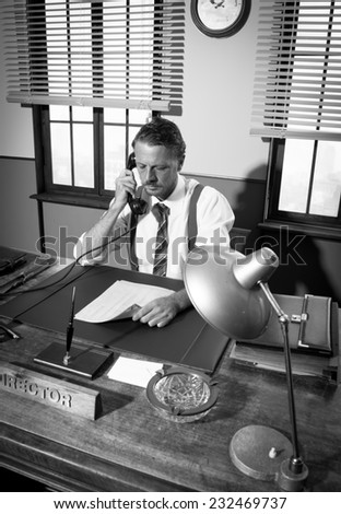 1950s office: confident director on the phone working at desk.