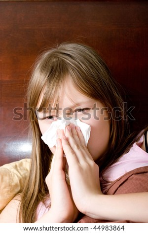 Sick with flu teenager girl in bed sneezing , allergy