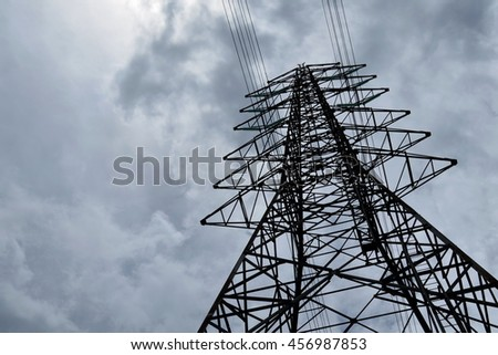Silhouette of electricity post on cloudy sky background,low angle view.