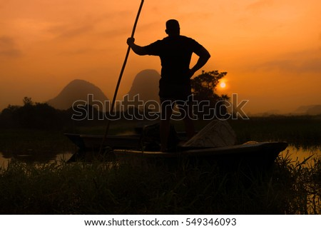 silhouette of fishermen standing in the boat with yellow and orange sun in the background