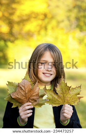 smiling child with autumn leaves