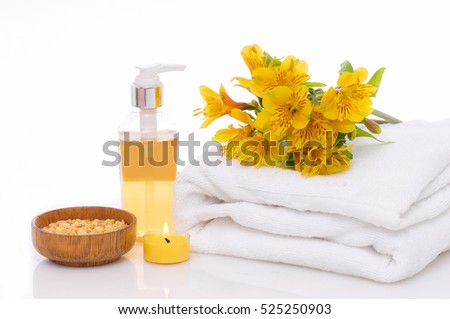 Spa setting with yellow orchid ,towel, oil,salt in bowl, candle