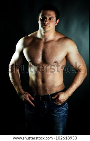 strong muscular athletic man on black background