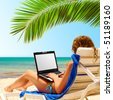 surfing on the beach. Laptop display is cut with clipping path - stock photo