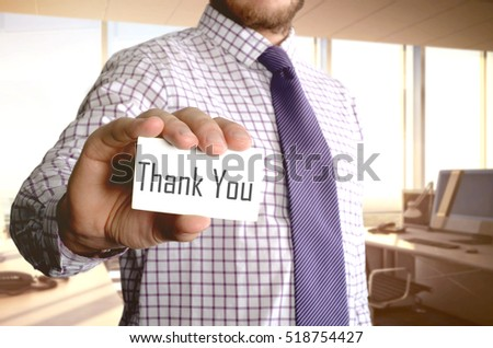 """ Thank you "" word on card hold by man"