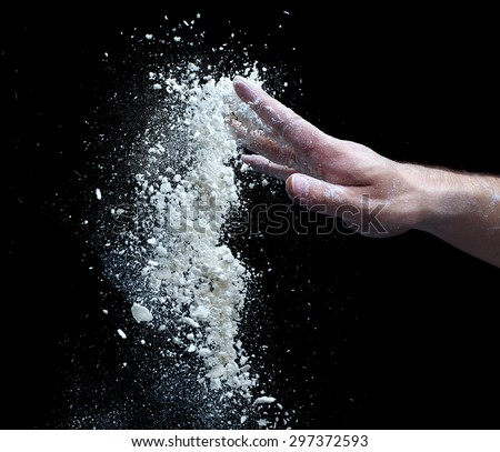 the man's hand and a handful of flour isolated on a black background