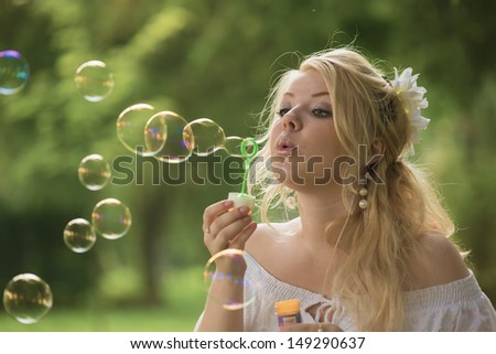 The young blonde blows soap bubbles