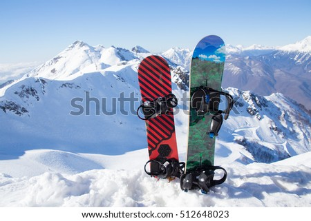 Two snowboard standing in the snow against the backdrop of the beautiful snow-capped mountains