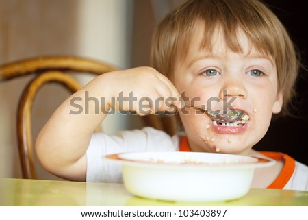 two-year child himself eats cereal with a spoon