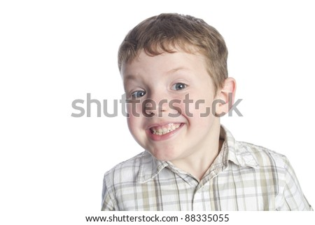 5 year old boy looking at camera and grinning. Shot on seamless white background. Room for text.