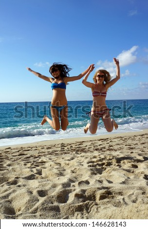 Young active women - girl friends high jump on a beach, Italy