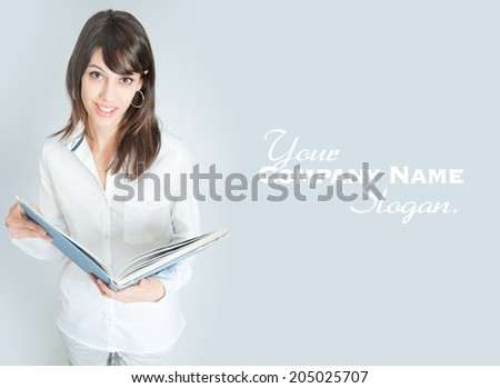 Young brunette wearing a white shirt reading a book