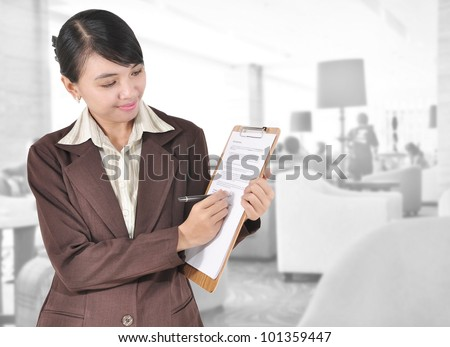Young businesswoman with pen and folder in the office