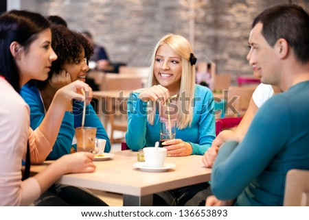 young teenagers friends drinking coffee in a cafe