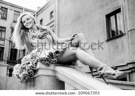 Young woman sitting on the ladder. Outdoors