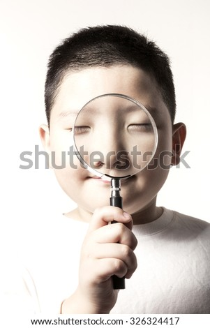 A asian(japan, chinese, korea) pretty boy(kid, children) hold a reading glasses(magnifying glass[lens], magnifier) and watch the something with questions isolated white at the studio.