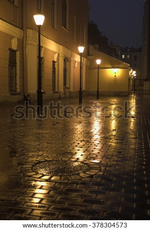 A back yard with street lamps and stone pavement in Saint Petersburg, Russia, at evening.