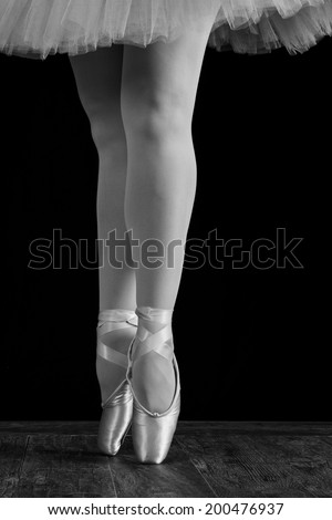 A ballet dancer standing on toes while dancing on black background