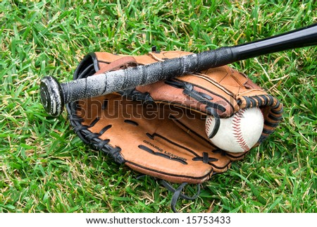 A baseball glove, ball and bat lie in the grass before a game.