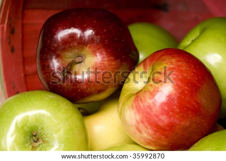 A basket full of shiny green and red apples spilling out, shallow depth of field, horizontal with copy space