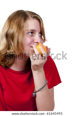 A beautiful and young teenage girl eating a peach