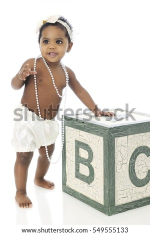 A beautiful baby girl standing with the help of a giant alphabet block.  She's wearing a white hair bow, strands of beads and a silky diaper cover.  On a white background.