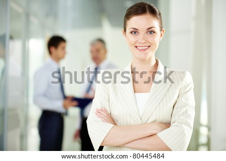 A beautiful businesswoman looking at camera with working men on background
