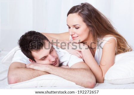 A beautiful caring woman lying on top of her sleeping husband