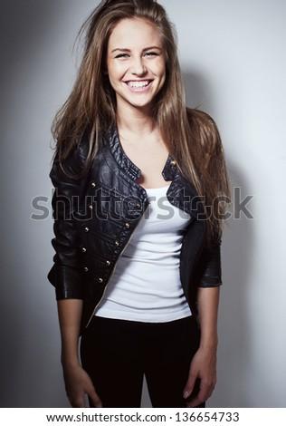 beautiful girl smile laughs in studio in black jacket - stock photo