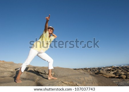 A beautiful looking mature woman standing confident and happy on a rock, isolated with ocean and clear blue sky as background and copy space.