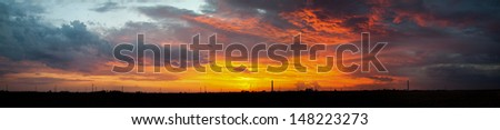 A beautiful midwest sunset panorama with clouds and silhouetted country landscape