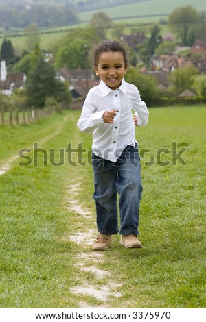 A beautiful mixed race little running up a hill in the English countryside and laughing