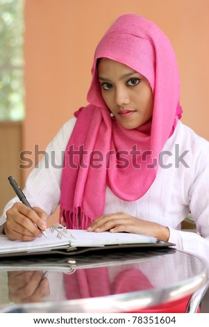 A beautiful muslim girls writing a diary book on the table