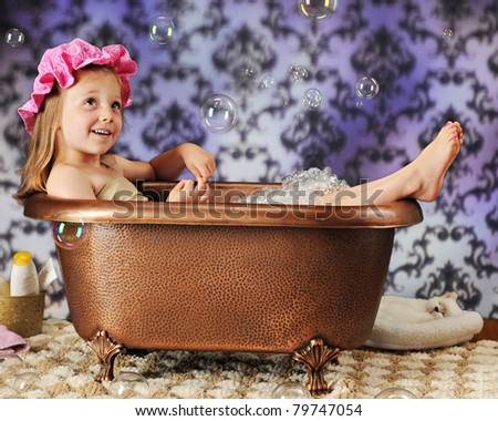 A beautiful preschooler in a bath bonnet and copper tub watching the air-born bubbles around her.