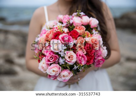 A  beautiful rose bouquet in bride hands on the sea background