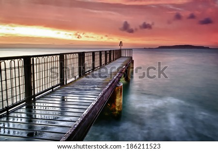 A beautiful sunrise over the Isle of Portland from a tiny pier at Bowleaze Cove in Weymouth.