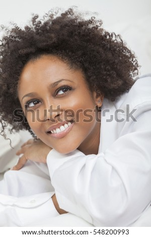 A beautiful thoughtful happy mixed race African American girl or young woman wearing a white shirt looking up smiling with perfect teeth