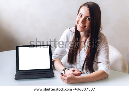 A beautiful young business lady makes a presentation sitting and smiling in front of a white table, uses a tablet with mockup screen