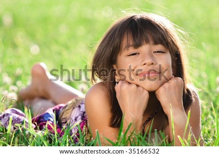 a beautiful young girl lays in a field smiling at the camera