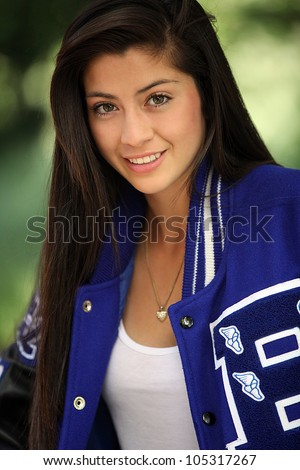 A beautiful young hispanic girl posing outdoors with her sports jacket on.