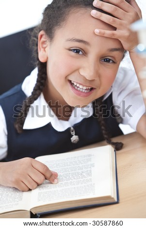 A beautiful young mixed race girl reading in a school classroom with a pile of books in front of her