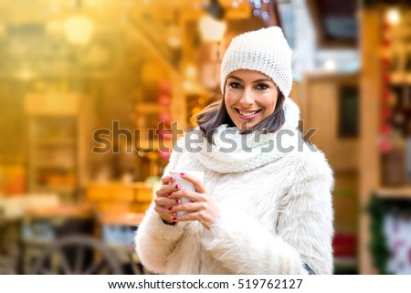 A beautiful young woman enjoying a cup of mulled wine on the christmas market.