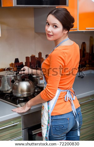 a beautiful young woman is putting a kettle
