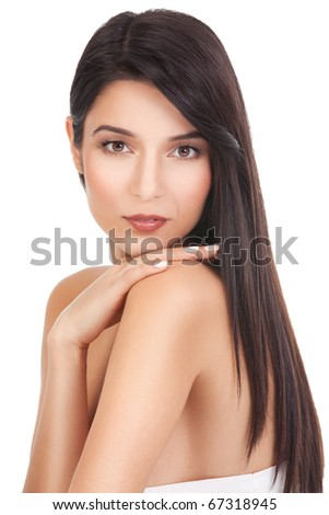 a beauty portrait of a young woman, shot on white background. she has long, dark brown hair; she looks over her shoulder, touching it with her hand.
