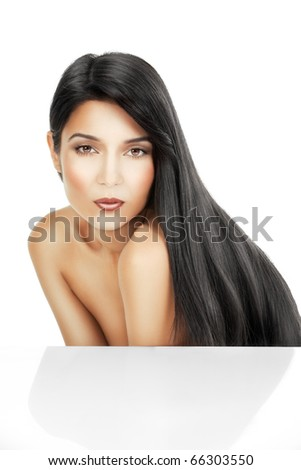 a beauty portrait of a young woman, shot on white background. she is bent forward and her long, black hair  flows on her back