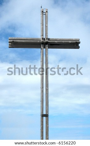 A big Cross on a mountain with sky